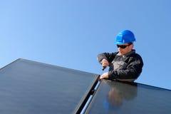 Man installing alternative energy photovoltaic pan royalty free stock photo