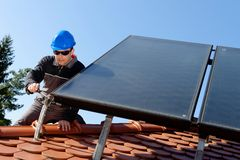 Man installing alternative energy photovoltaic pan Stock Photography