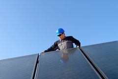 Man installing alternative solar energy photovolta. Man installing alternative energy photovoltaic solar panels on roof Royalty Free Stock Photography