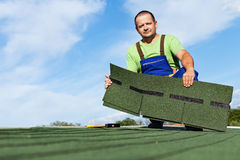 Man installing bitumen roof shingles Stock Photo