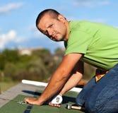 Man installing bitumen roof shingles Royalty Free Stock Photo
