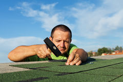 Man installing bitumen roof shingles Stock Images