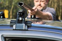 Man installing a car roof rack outdoors. Middle-aged man installing a car roof rack outdoors royalty free stock photo