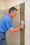 Man installing ceramic tile in bathroom. Man installing ceramic tile on wall in shower area of bathroom stock photo