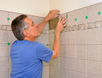 Man installing ceramic tile in bathroom Stock Photography