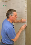 Man installing ceramic tile border Royalty Free Stock Photo