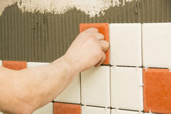 Man installing ceramic tile Royalty Free Stock Images