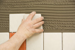 Man installing ceramic tile. On a wall Stock Images