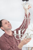 Man installing chandelier Royalty Free Stock Photos