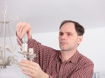 Man installing chandelier Royalty Free Stock Photo