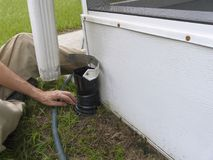 Man Installing Residential Downspout Connectors. A man is installing a connector between the downspout and drainage pipe on his house to seal out debris and royalty free stock image