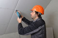 Man installing drywall. Using cordless drill Royalty Free Stock Images
