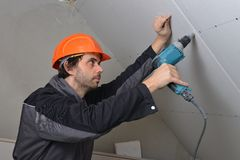 Man installing drywall. Using drill Royalty Free Stock Photography