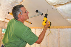Man installing drywall on ceiling. Man using cordless drill to hasten drywall panel to ceiling royalty free stock photo