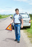 Man installing emergency sign on road near his car Stock Photography