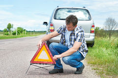 Man installing emergency sign on road near his car Royalty Free Stock Photography