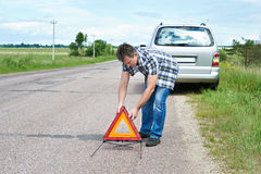 Man installing emergency sign on road near his car Stock Image