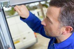 Man installing garage door Royalty Free Stock Image