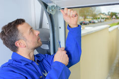 Man installing garage door. Man installing a garage door stock photo