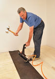 Man installing hardwood floor using nailer. Man installing hardwood floor using pneumatic power nailer stock photo