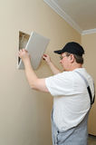 Man is installing hatch on the wall. Stock Photography