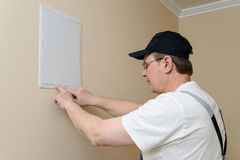 Man is installing hatch on the wall. Royalty Free Stock Photo