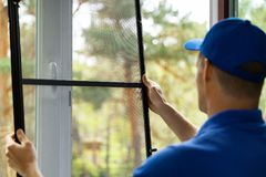 Man installing insect mesh screen to protect room from mosquito royalty free stock photos