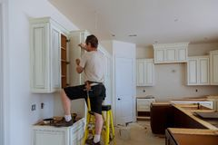 Man installing kitchen cabinets door. Installation of kitchen royalty free stock photo