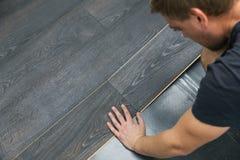 Man installing laminate floor royalty free stock photography