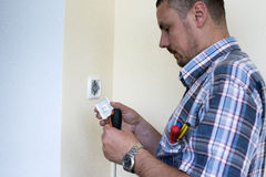 Man installing light switch Royalty Free Stock Images
