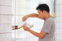 Man installing light switch Stock Image