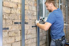 Man installing metal profile frame on the old brick wall royalty free stock photography