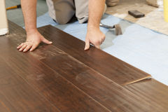 Man Installing New Laminate Wood Flooring. Abstract stock photography