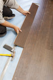 Man Installing New Laminate Wood Flooring Stock Images