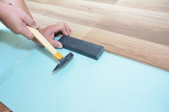 Man Installing New Laminate Wood Flooring. Worker Installing wooden laminate flooring with hammer. Handyman laying down laminate Royalty Free Stock Photos
