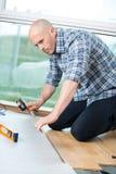 Man installing new laminated wooden floor royalty free stock photo