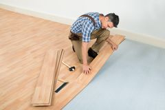 Man installing new laminated wooden floor Royalty Free Stock Images