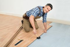Man installing new laminated wooden floor. Carpenter Installing New Laminated Wooden Floor At Home royalty free stock photos
