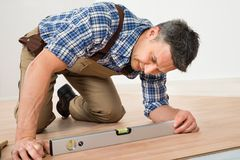 Man installing new laminated wooden floor. Carpenter Installing New Laminated Wooden Floor At Home royalty free stock photography