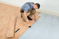 Man installing new laminated wooden floor Stock Photos