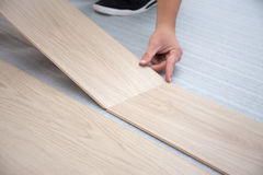 Man installing new laminated wooden floor. Male hands installing new laminated wooden floor royalty free stock photography