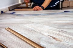 Man installing new wooden laminate flooring at home. Man installing new wooden laminate flooring at home royalty free stock photo