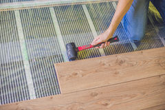 Man installing new wooden laminate flooring. infrared floor heat. Man installing new wooden laminate flooring on a warm film floor. infrared floor heating system royalty free stock photography