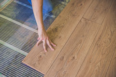 Man installing new wooden laminate flooring. infrared floor heat. Man installing new wooden laminate flooring on a warm film floor. infrared floor heating system stock image