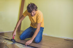 Man installing new wooden laminate flooring. infrared floor heat royalty free stock image