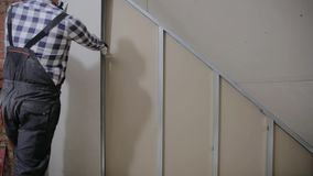 Man installing plasterboard sheet to wall for attic room construction stock video footage