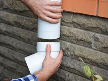 Man installing plastic rain gutter system pipeline. Guttering, Gutters, Plastic Guttering, Guttering & Drainage by Handyman hands. Guttering Down pipe Fittings Stock Photo