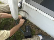 Man Installing Residential Downspout Connector DIY. A man is installing a connector between the downspout and drainage pipe on his house to seal out debris and royalty free stock photography
