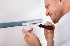 Man Installing Security System Door Sensor. Close-up Of Technician Installing Security System Door Sensor Using Screwdriver Royalty Free Stock Images