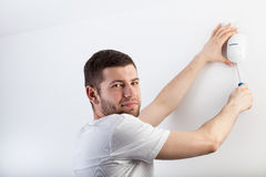 Man installing a security system. In his house Stock Image